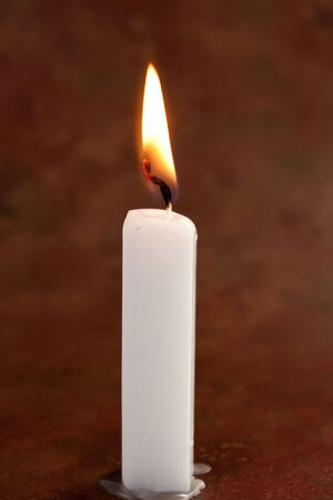 White lit candle on antique background