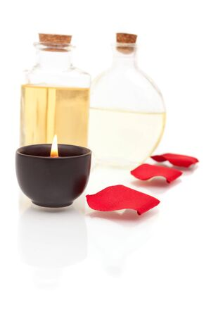 Aromatherapy oils, rose petals and candle on white background