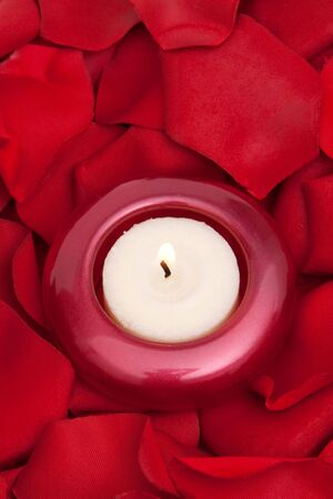 Candle surrounded with red rose petals Stock Photo - 6810336
