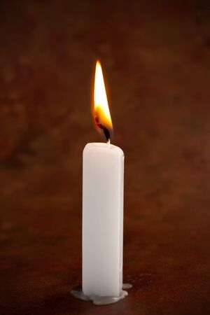 candle: White lit candle on antique background