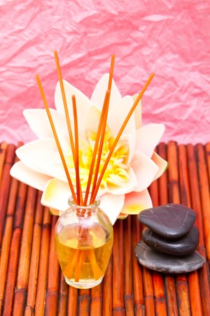 Spa oils, hot massage stones and lotus on bamboo mat