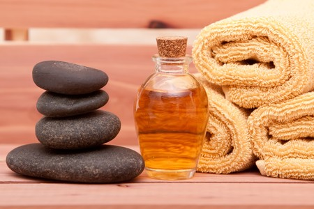 Aromatherapy oil, spa towels and lastone therapy rocks
