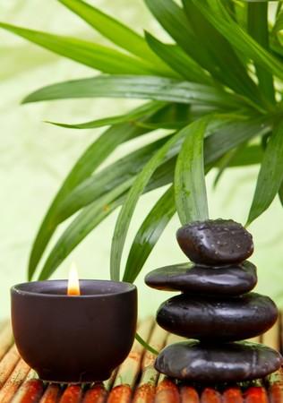 Evenwichtige steentjes met aromatherapy kaars en bamboe bladeren