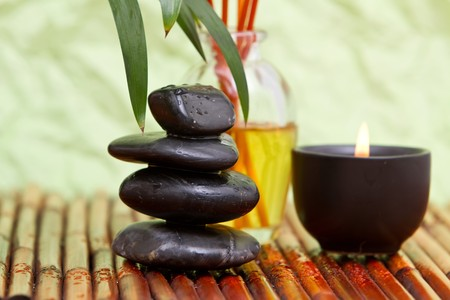 Various spa and massage items on bamboo mat
