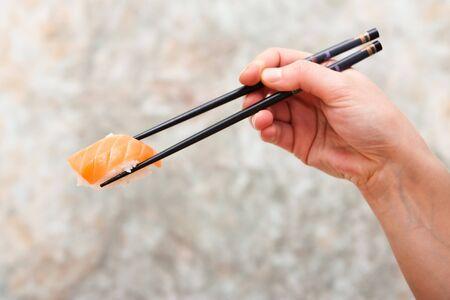 연어 초밥을 젓가락으로 들고