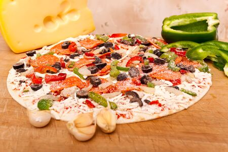 bell peppers: Raw pizza with pepperoni, bell peppers, black olives and onions
