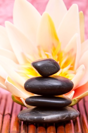 Hot massage stones and water lily on bamboo mat photo