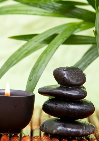 Balanced pebbles with aromatherapy candle and bamboo leaves Stock Photo