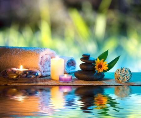 spa stone: drei Kerzen und Handt�cher schwarzen Steinen und orange G�nsebl�mchen auf dem Wasser Lizenzfreie Bilder