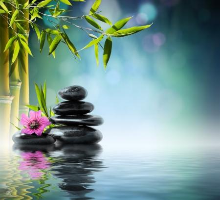 massage: Turm aus schwarzem Stein und Hibiskus mit Bambus auf dem Wasser