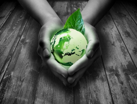 environmental protection: green world in the heart hand - grass background