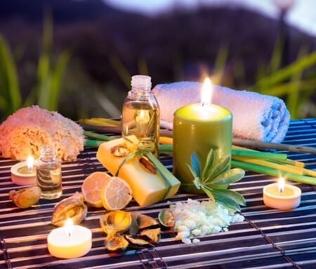 lemon soap , oil, towel, salt and candles in garden  Stock Photo