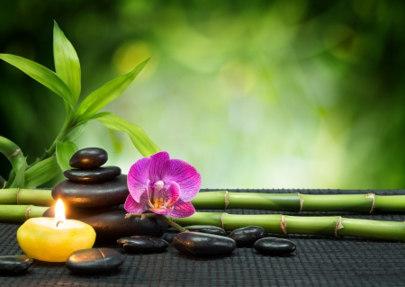 white stone: purple orchid, candle, with stones , bamboo on black mat  Stock Photo