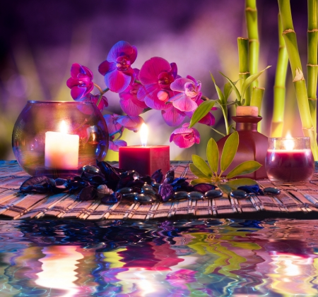 pink orchid: violet composition - candles, oil, orchids and bamboo on water  Stock Photo