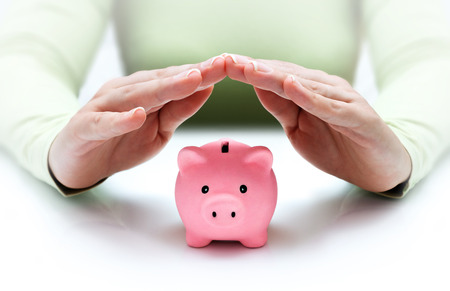 protect your savings - with his hands covering the piggy bank  photo