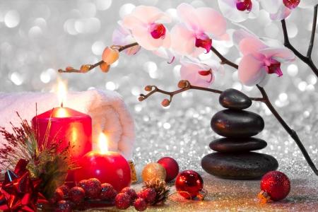 composition de massage spa de Noël avec des bougies, des orchidées, des pierres