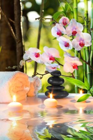 bambou: composition de massage spa avec des bougies, des orchidées, des pierres dans le jardin Banque d'images