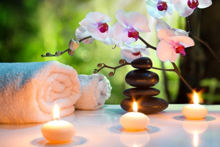 zen stones: massage composition spa with candles, orchids, stones in garden
