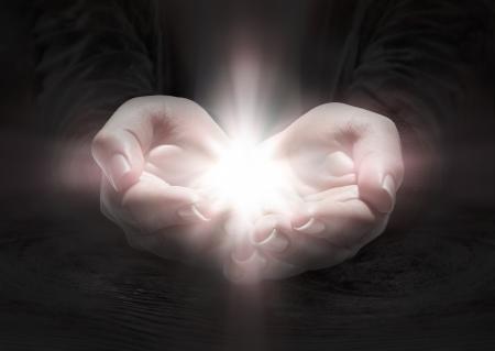 Lumière dans les mains - prier le crucifix dans l'obscurité Banque d'images - 25451336