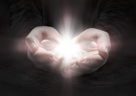 milagro: luz en las manos - rezar el crucifijo en la oscuridad Foto de archivo