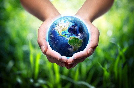 earth pollution: earth in hands - grass background - environment concept