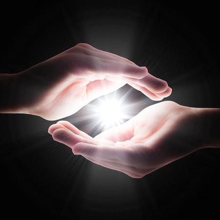 white light: luz cruz en la oscuridad en sus manos Foto de archivo