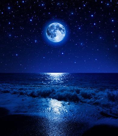 super maan in sterrenhemel op zee strand