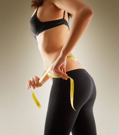 Girl measuring her waist with tape measure  photo