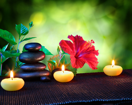alternative wellness: candles and stones spa composition - with hibiscus