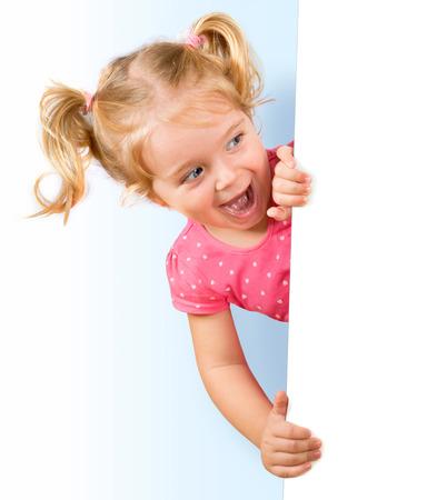 Sourire petite fille regardant derrière un tableau blanc Banque d'images