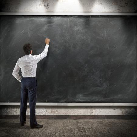 businessman presents a written report on a blackboard