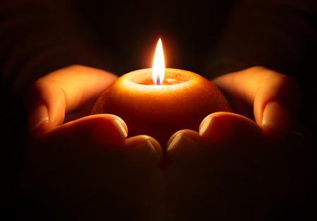 祈りの手の中のろうそく 写真素材