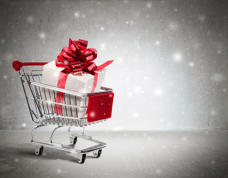 christmas gift in cart - wall and snow Standard-Bild
