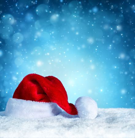 santa clause hat: santa clause hat with snow and blue snowfall background Stock Photo