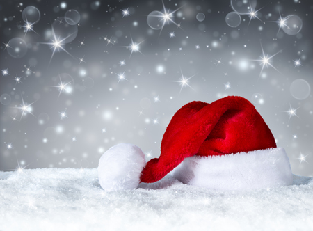 christmas decorations with white background: Santa Claus hat with snow and silver snowfall background Stock Photo