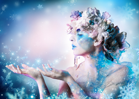 ice queen: Winter portrait of woman blowing snowflakes