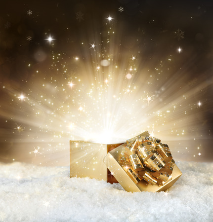open present: magic shining of christmas gift - golden stardust and snow