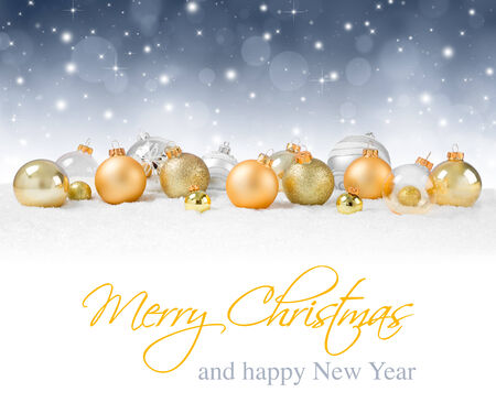 golden baubles on snow with silver sparkle background photo