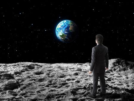 businessman walks on moon surface Stock Photo