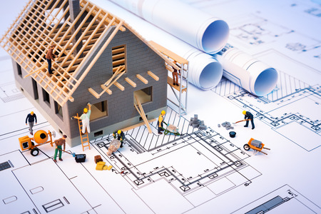 building: building house on blueprints with worker  construction project Stock Photo