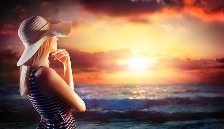 mujer mirando el horizonte: mujer que mira en puesta de sol en las vacaciones de verano el mar