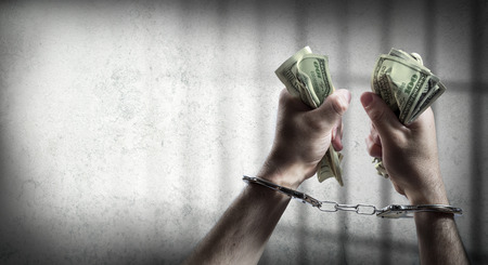gripping bars: arrest for corruption  man handcuffed holding dollars