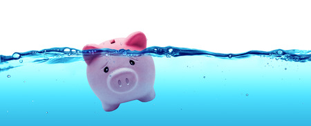 Piggy bank drowning in debt  savings to risk Фото со стока