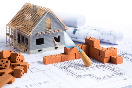 huis in de bouw project met bakstenen en blauwdruk