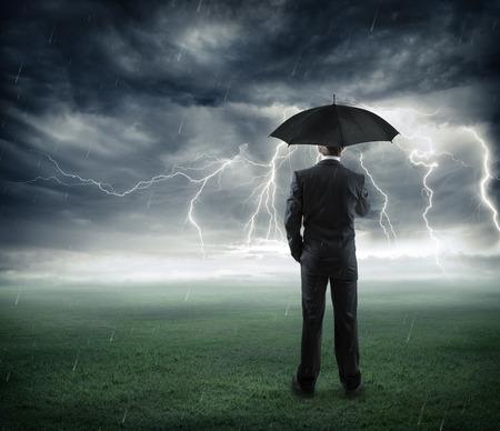 risk and crisis  businessman below storm with umbrella