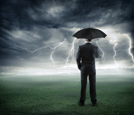 risk and crisis  businessman below storm with umbrella