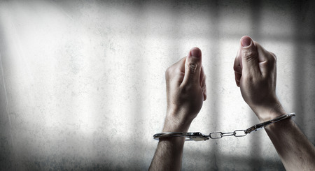 arrest  man handcuffed in cell prison
