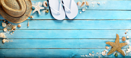 seashells on blue wooden plank with straw hat and flipflop