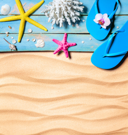 seashell: flip-flop, starfish, seashells and coral on wooden and sand as beach background