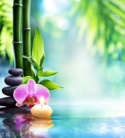spa martwa natura - Świeca i kamień z bambusa w naturze na wodzie